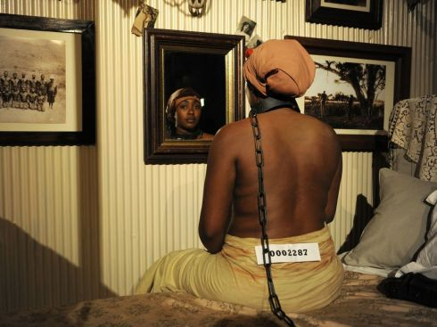 "A Place in the Sun, from Brett Bailey's ""Exhibit B"". This installation was based on an account of a French colonial officer who kept black women chained to his bed, exchanging food for sexual services."